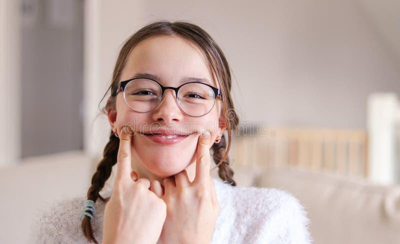 Portret elegancka szalenie atrakcyjna uśmiechnięta preteen dziewczyna w szkłach z pigtails robi sztucznemu uśmiechowi palcami na  zdjęcie stock