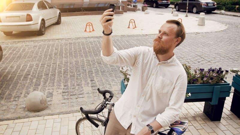 Portret elegancki modnisia mężczyzna robi selfie na rocznika bicyklu fotografia royalty free