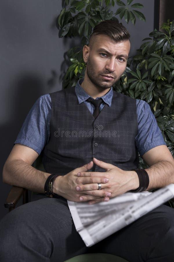 Portret elegancki przystojny mężczyzna w krześle z gazetą Atrakcyjny brutalny ufny biznesmen zdjęcie royalty free