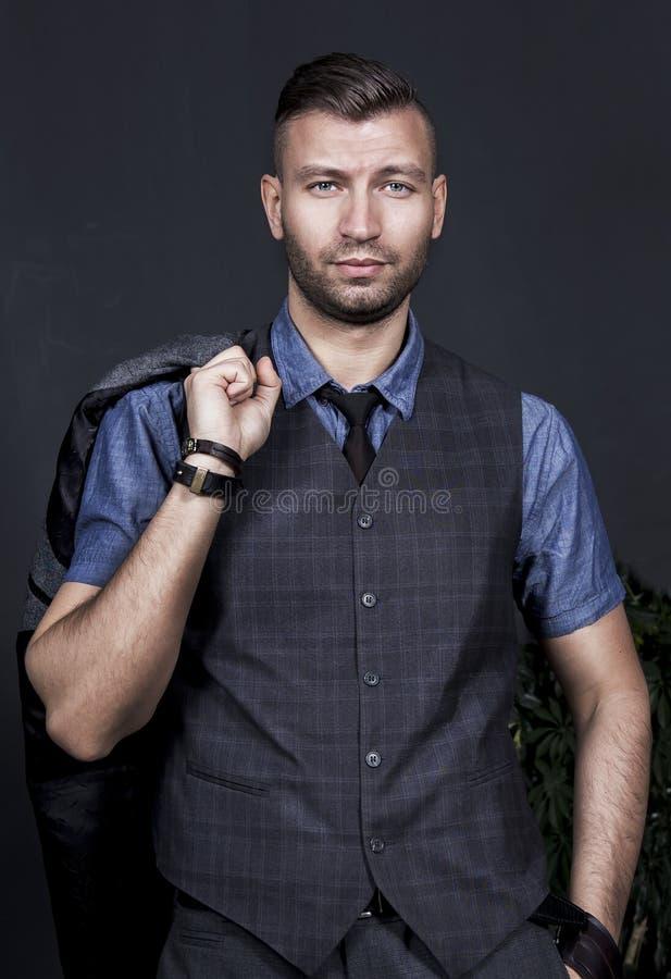 Portret elegancki przystojny młody facet z modnym uczesaniem trzyma kurtkę na jego ramieniu Biznesowy mężczyzna w krawacie i kami obrazy royalty free