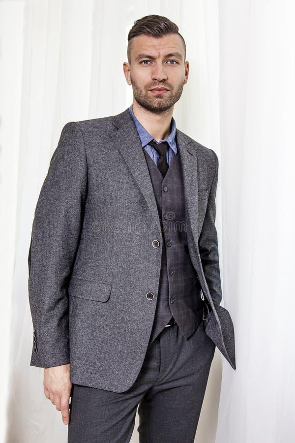 Portret elegancki ufny przystojny mężczyzna w garniturze blisko okno spojrzeń przy ramą obraz stock