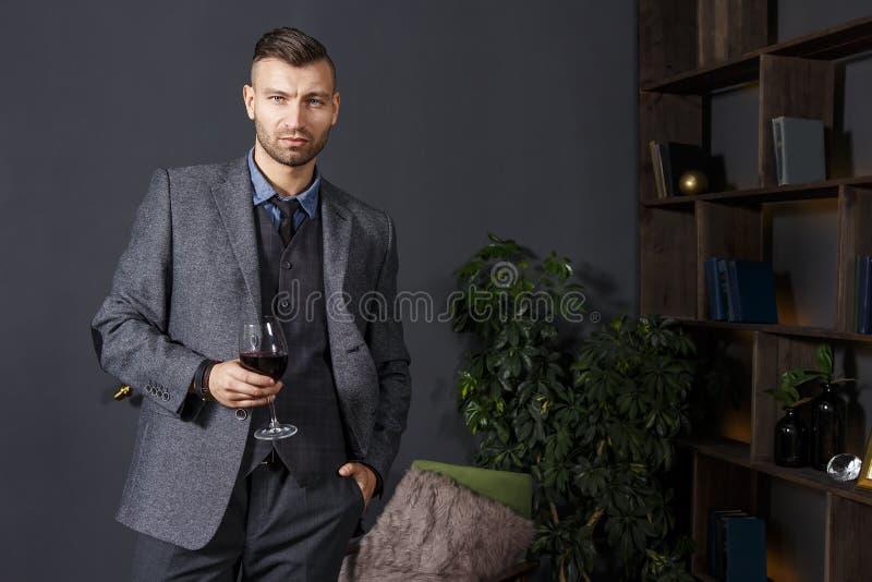 Portret elegancki ufny przystojny mężczyzna w garniturze z szkłem czerwone wino w luksusowym wnętrzu obrazy royalty free