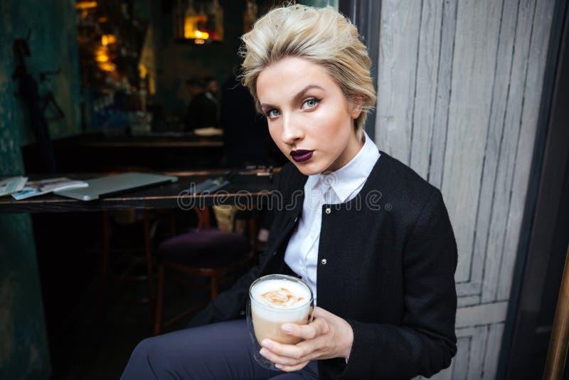 Portret eleganckiej kobiety samotny obsiadanie przy kawiarnią zdjęcie royalty free