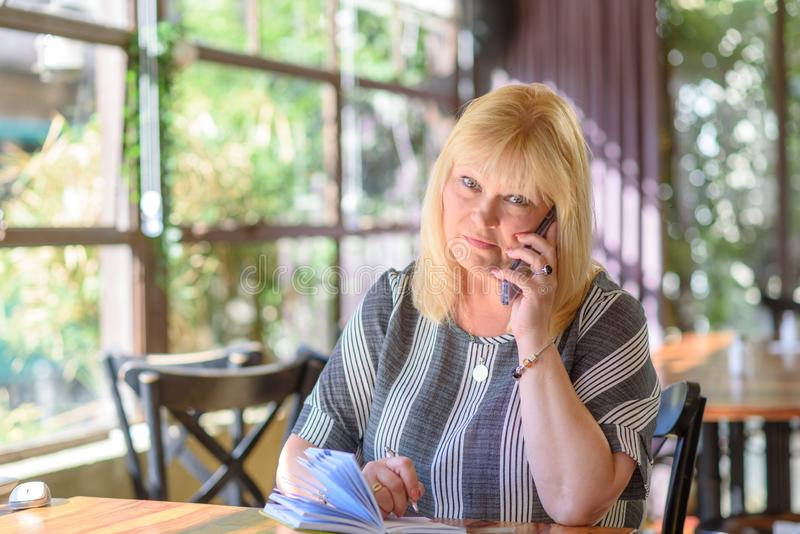 Portret elegante midden oud plus grootteonderneemster in bureau die op telefoon spreken royalty-vrije stock afbeeldingen