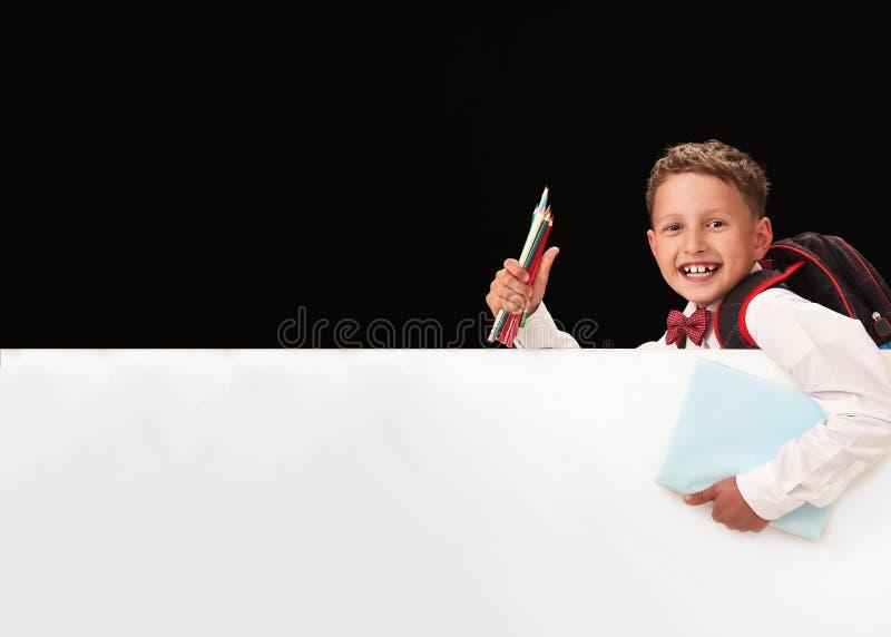 Portret emocjonalny dziecko uczeń ono uśmiecha się, szczęśliwy wracać szkoła pojęcia o uczniu trzymać białego sztandar zdjęcia stock