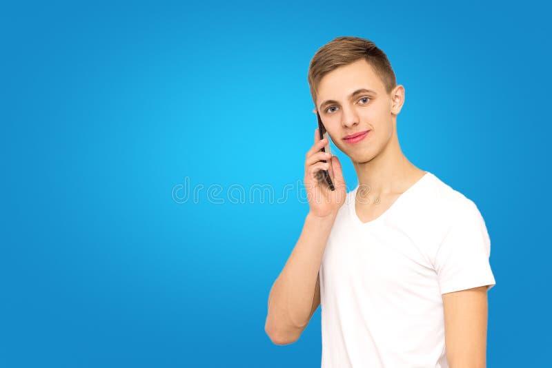 Portret facet opowiada na telefonie w studiu na błękitnym tle, odizolowywa, mężczyzna na błękitnym tle fotografia royalty free
