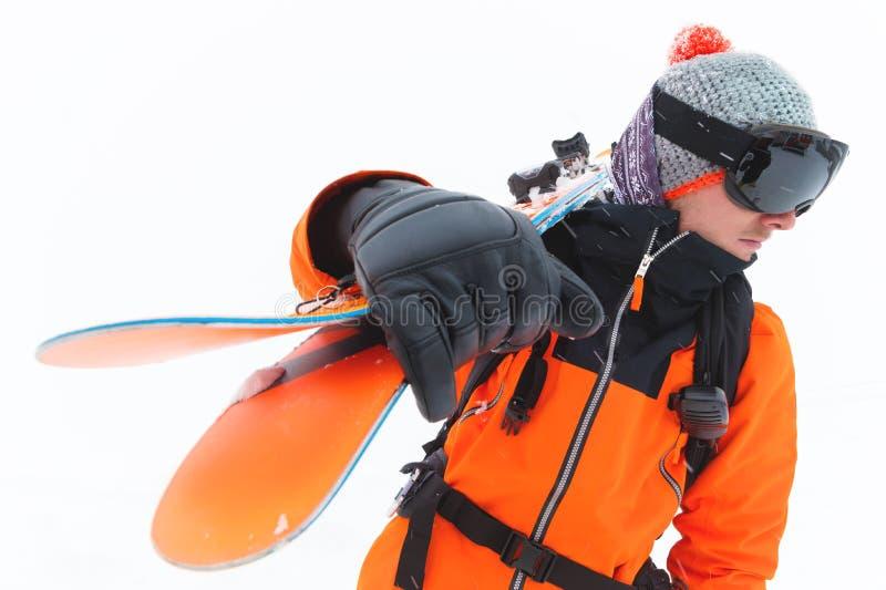 Portret fachowa atlety narciarka jest ubranym czarny maskowego w pomarańczowej kurtce z nartami na jego naramiennych spojrzeniach fotografia royalty free