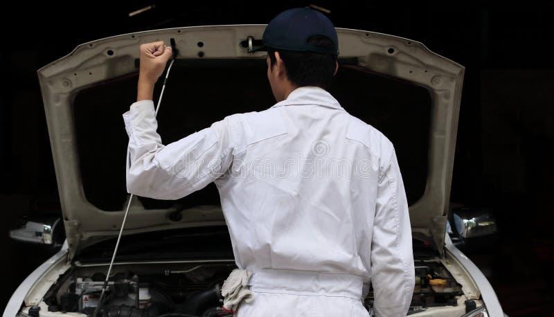 Portret fachowy młody mechanika mężczyzna w jednolitych dźwiganie rękach przy remontowym garażem tła samochodowy pojęcia ubezpiec fotografia stock