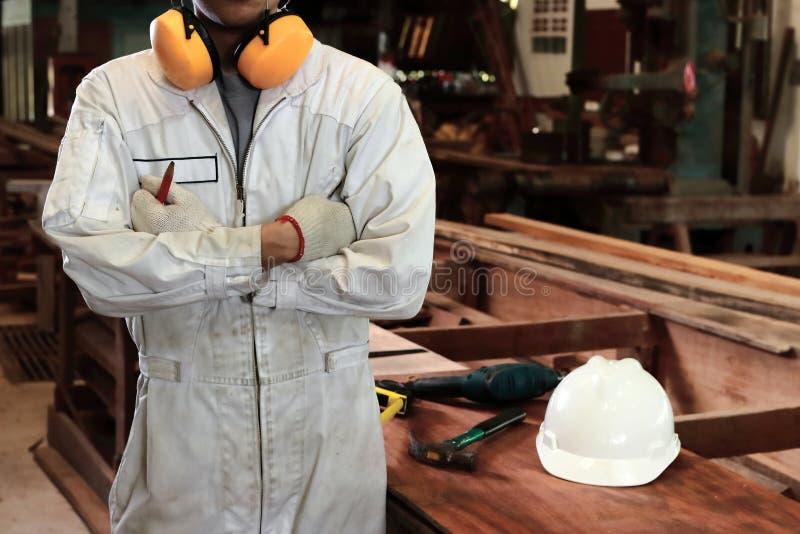 Portret fachowy młody pracownik z bezpieczeństwo munduru krzyża jeden ` s ręką nad klatką piersiową w ciesielka warsztacie zdjęcia stock