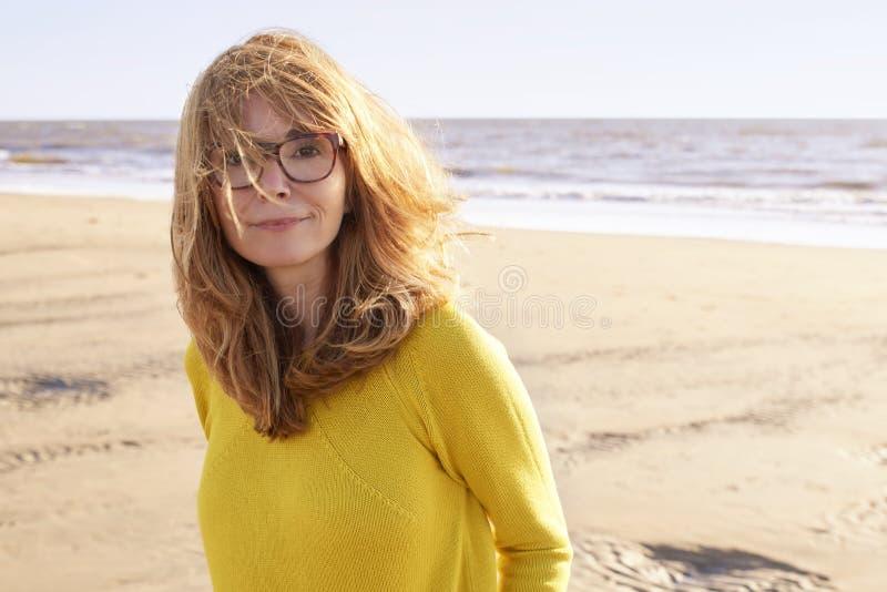 Portret fizzy z włosami piękna kobiety pozycja na plaży obrazy stock