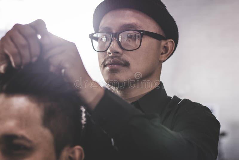 Portret fryzjer męski fryzura kostiumowy włosy z ręką i pomaduje w zakładzie fryzjerskim lub salonie zdjęcie royalty free