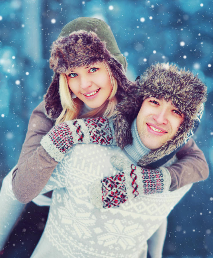 Portret gelukkig glimlachend jong paar in de winterdag die pret, man hebben die op de rug rit geven aan vrouw over sneeuwvlokken stock fotografie