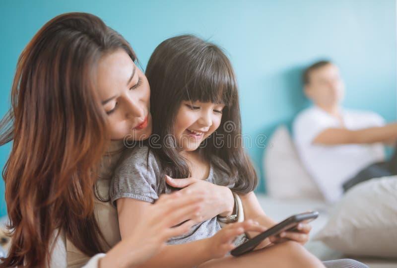 Portret Gelukkige Dochter het spelen smartphone met haar moeder royalty-vrije stock afbeelding