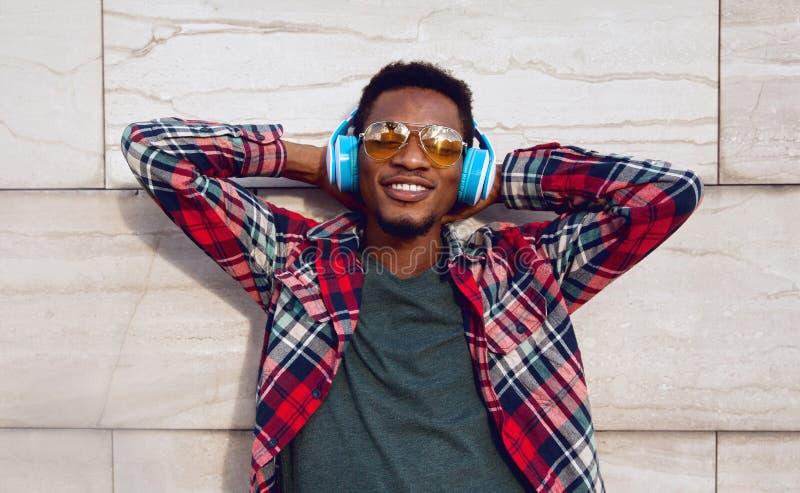 Portret gelukkige glimlachende Afrikaanse mens met het draadloze hoofdtelefoons genieten die aan muziek in stad op grijze muurach royalty-vrije stock afbeelding