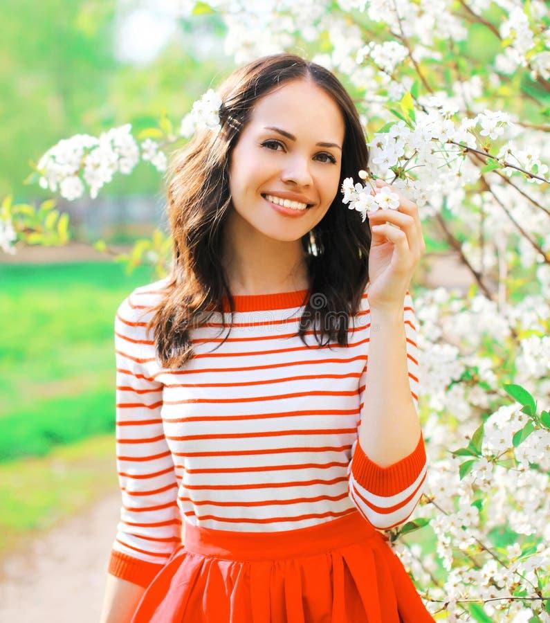 Portret gelukkige glimlachende vrouw in de tuin van de lentebloemen stock fotografie