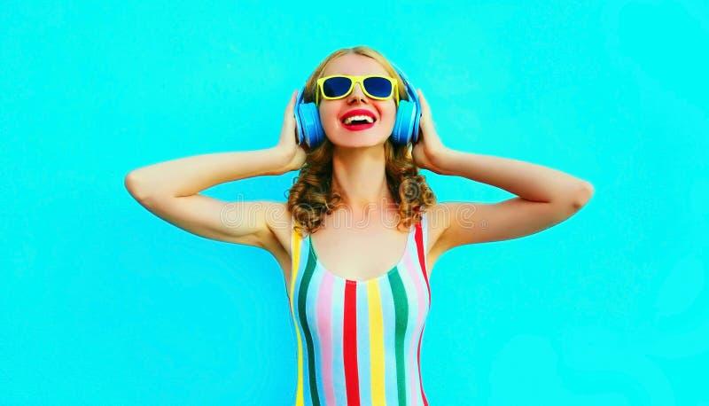 Portret gelukkige glimlachende vrouw die aan muziek in draadloze hoofdtelefoons op kleurrijk blauw luisteren stock afbeeldingen