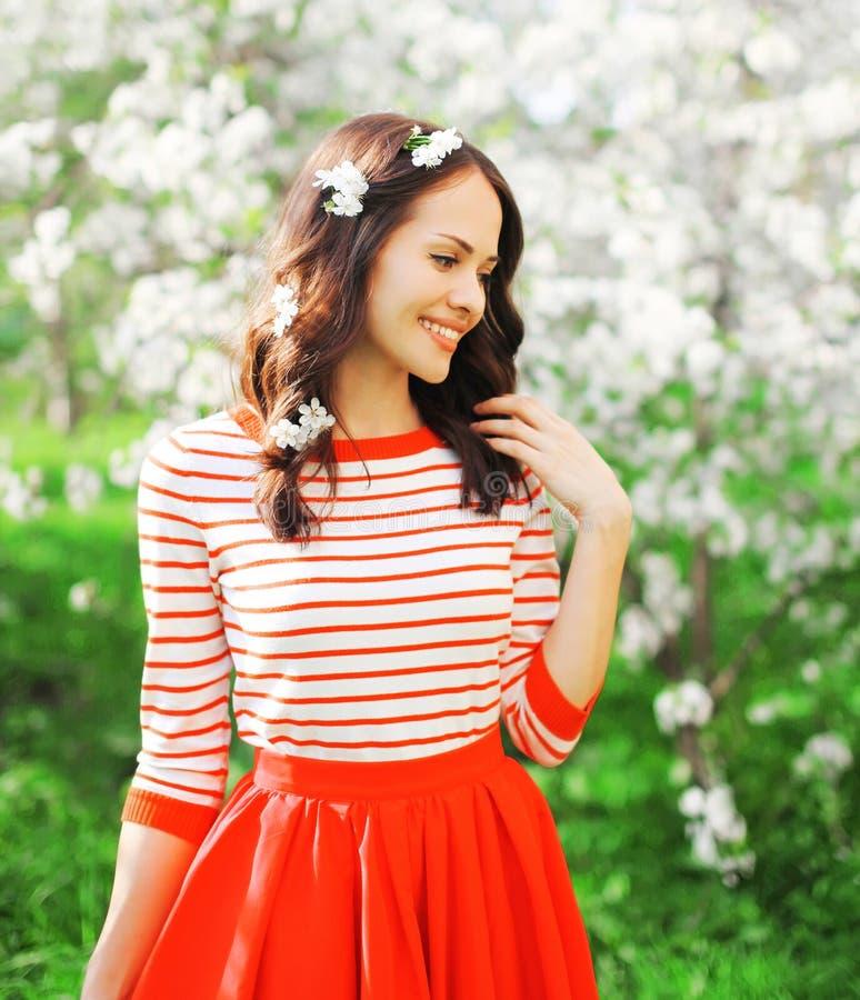 Portret gelukkige glimlachende vrouw met bloemblaadjes in haar haar bij de lentebloemen stock afbeeldingen