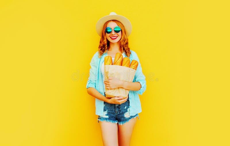 portret gelukkige het glimlachen het document van de vrouwenholding zak met lange witte broodbaguette, die strohoed, borrels op k stock afbeelding