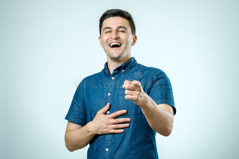 Portret gelukkige jonge mens, het lachen, die met vinger richten bij wat royalty-vrije stock foto's