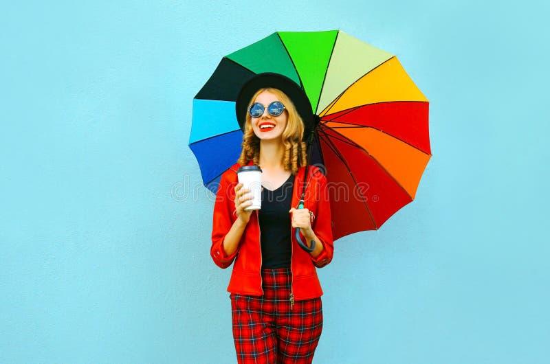 Portret glimlachende vrouw die kleurrijke paraplu, hete koffiekop houden, die rood jasje, zwarte hoed op blauwe muur dragen stock afbeelding