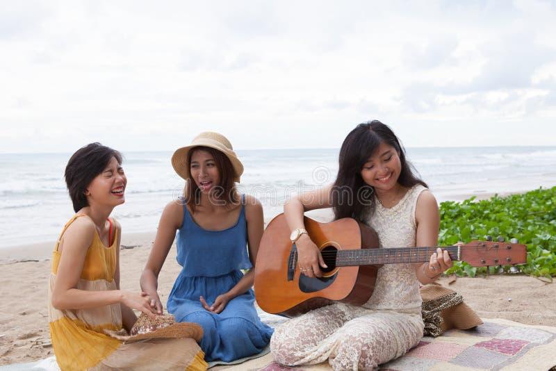 Portret grupa młoda azjatykcia kobieta bawić się gitarę w morze plaży obraz royalty free