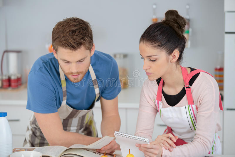 Portret het gelukkige jonge paar koken samen in keuken royalty-vrije stock afbeelding