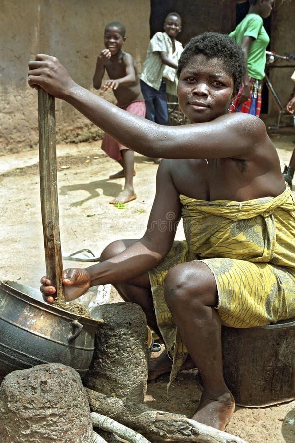 Portret het Ghanese Vrouw koken in openluchtkeuken stock foto