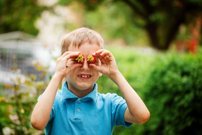 Portret het glimlachen de aardbei van de jongensholding vóór zijn ogen op de aardachtergrond stock afbeelding