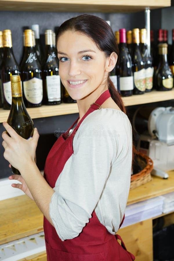 Portret het glimlachen de flessen witte wijn van de serveersterholding royalty-vrije stock foto