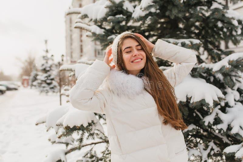 Portret het mooie leuke meisje koelen op zonneschijn in bevroren ochtend Jonge blije vrouw die de winter van tijd op sparren geni royalty-vrije stock afbeelding