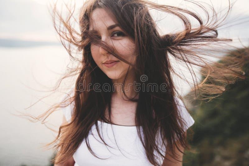 Portret hipsterki z wietrznymi włosami stojącej na górze skalnej z pięknym światłem słonecznym na rzece. atmosferyczny fotografia stock