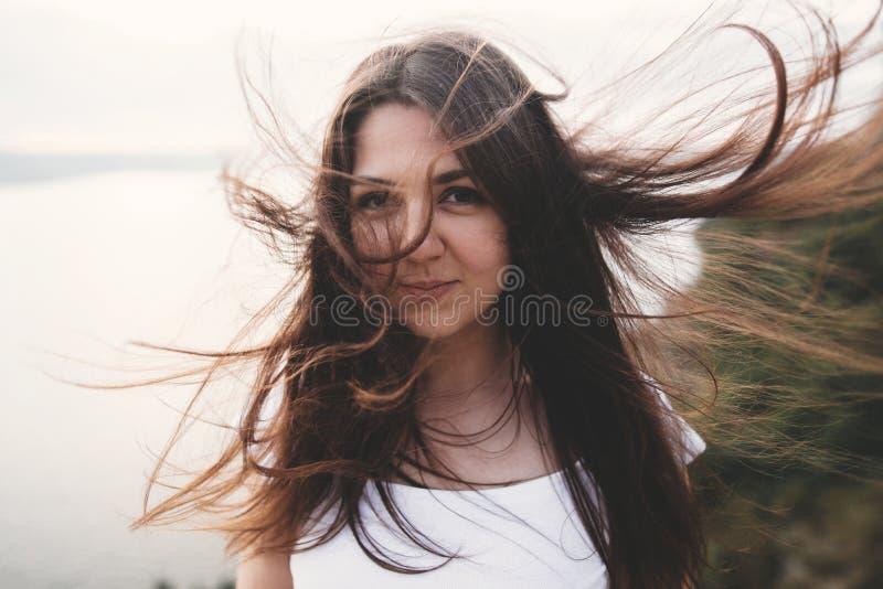 Portret hipsterki z wietrznymi włosami stojącej na górze skalnej z pięknym światłem słonecznym na rzece. atmosferyczny obraz stock