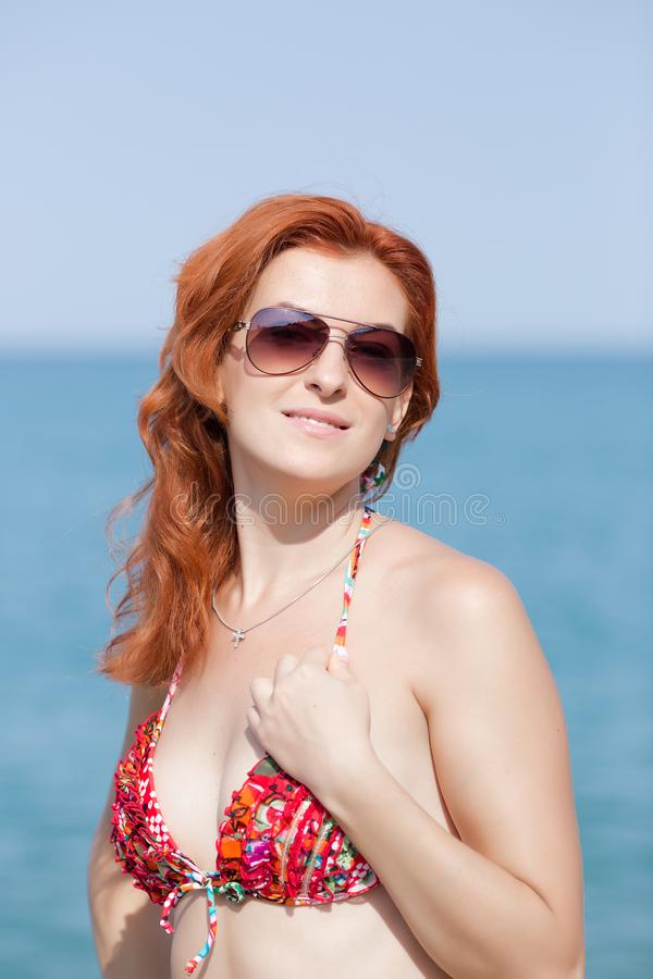 Portret imbirowa dziewczyna w okularach przeciwsłonecznych przy morzem fotografia stock