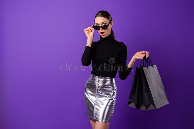 Portret imponująca kobieta dotyka jej eyewear eyeglasses mienia krzyczące rozkrzyczane torby odizolowywać nad purpurowym fiołkiem obraz stock