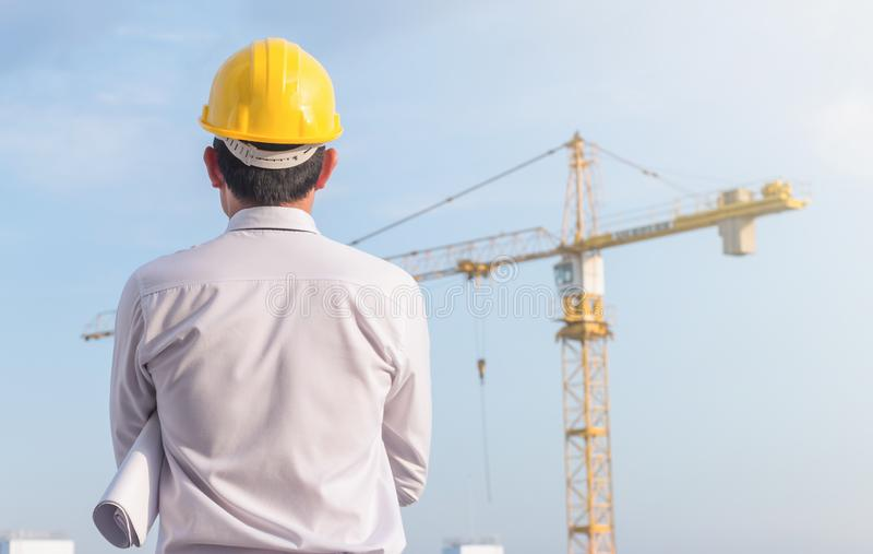 Portret inżynier odzieży hełma żółty bezpieczeństwo i trzymać projekt przy budową z dźwigowym tłem zdjęcie stock