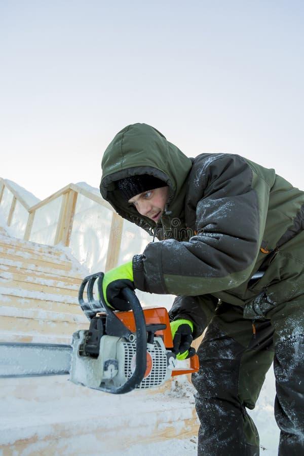 Portret instalator w pomarańczowej kamizelce z piłą łańcuchową w jego ręki zdjęcie stock