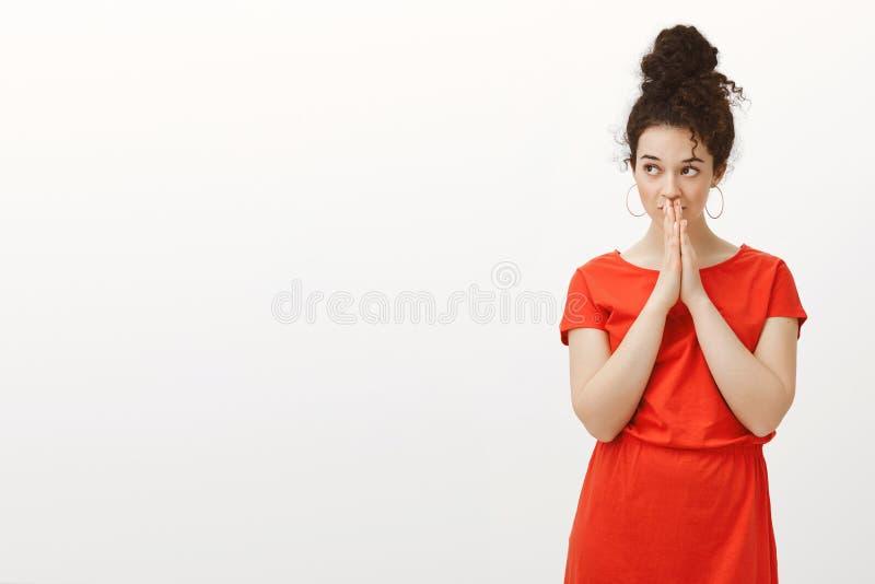 Portret intensywna skołatana atrakcyjna kobieta w ślicznej przypadkowej czerwieni sukni, trzymający rękę wewnątrz ono modli się,  obrazy royalty free