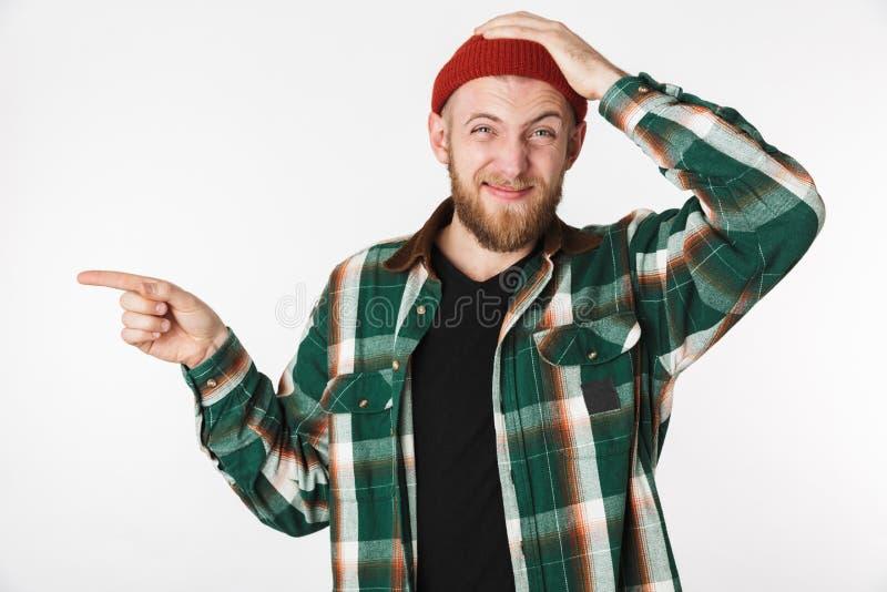 Portret intrygujący facet jest ubranym kapeluszu, szkockiej kraty koszula i, podczas gdy stojący nad bielem zdjęcia royalty free