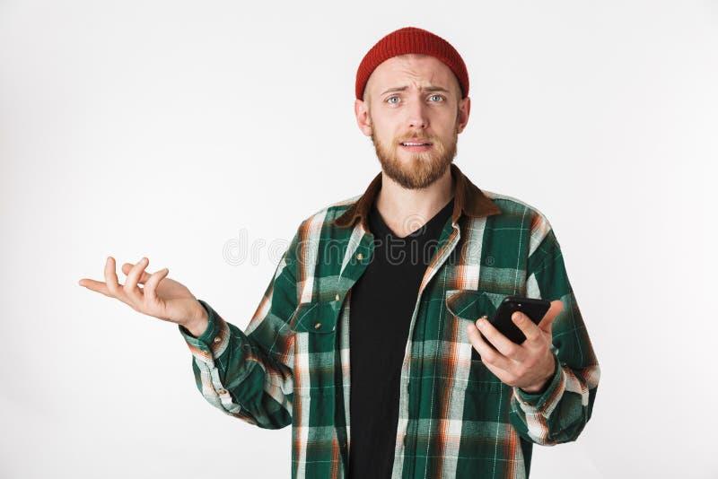 Portret intrygujący mężczyzna jest ubranym kapeluszu i szkockiej kraty koszula używać telefon komórkowego, podczas gdy stać odizo zdjęcia royalty free