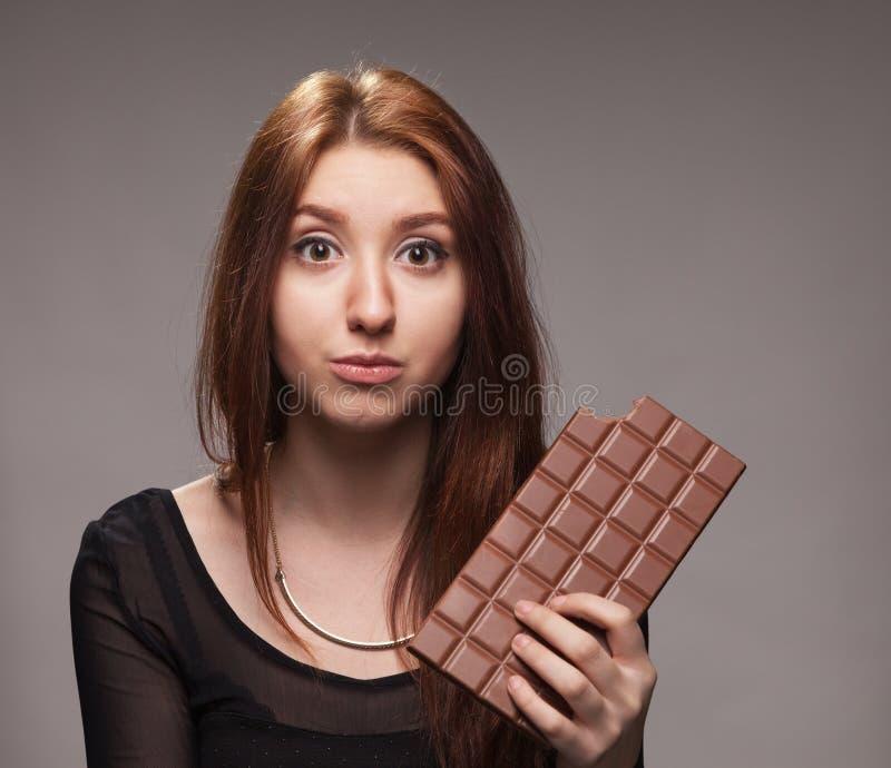 Portret intrygująca młoda dziewczyna z dużą czekoladą obrazy stock