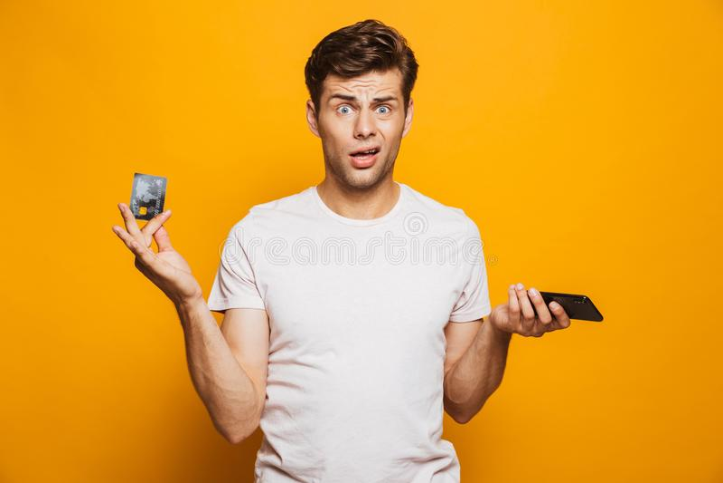Portret intrygujący młodego człowieka mienia telefon komórkowy obrazy stock