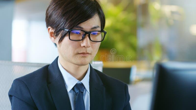Portret Japoński biznesmen Jest ubranym szkła, Siedzi przy obrazy stock