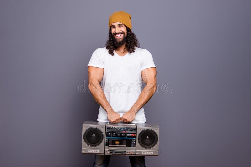 Portret jego on ładny przystojny atrakcyjny rozochocony z włosami faceta mienie w ręka rocznika retro gracza głośnym uderzeniu obraz stock