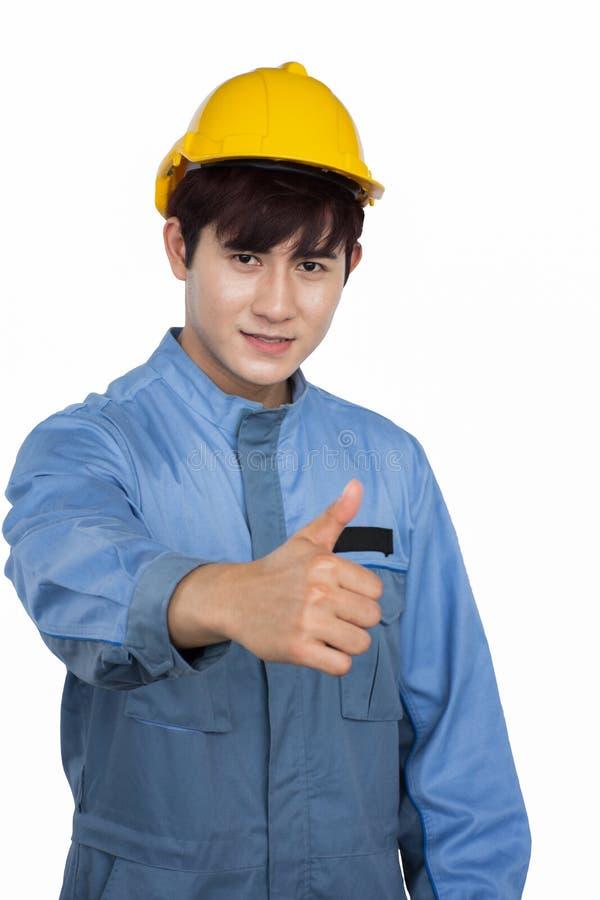 Portret jest ubranym żółtego hełm w Jednolitym mechaniku młody pracownik budowlany zdjęcia royalty free