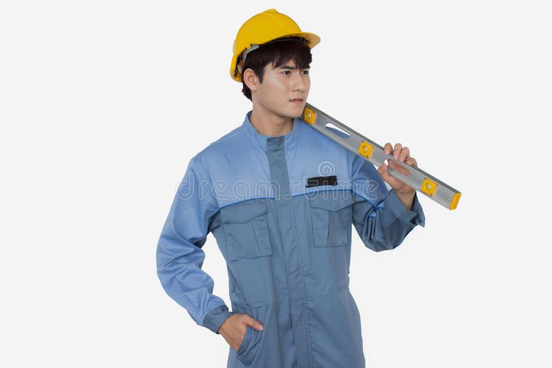 Portret jest ubranym żółtego hełm w Jednolitym mechaniku młody pracownik budowlany trzyma poziom zdjęcie royalty free
