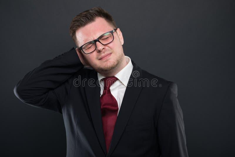 Portret jest ubranym czarnego kostium gestykuluje tylną obolałość biznesowy mężczyzna zdjęcie royalty free