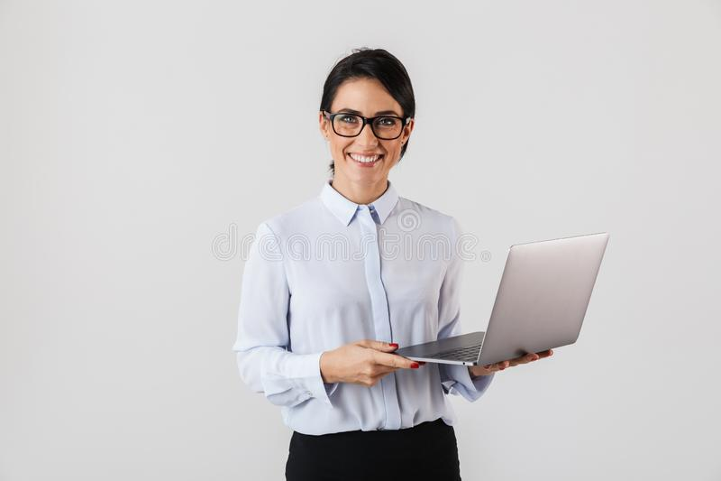 Portret jest ubranym eyeglasses trzyma srebnego laptop w biurze młody bizneswoman, odizolowywający nad białym tłem obraz royalty free