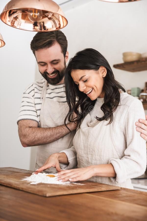 Portret jest ubranym fartuchy gotuje ciasto z mąką i jajkami w kuchni w domu caucasian para zdjęcie stock