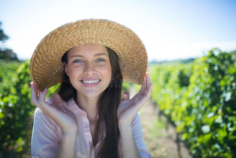 Portret jest ubranym kapelusz na słonecznym dniu przy winnicą piękna młoda kobieta zdjęcia royalty free