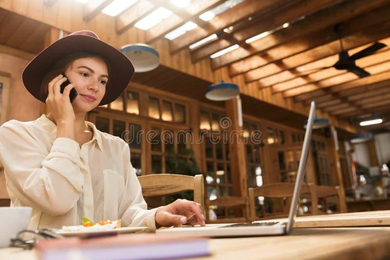 Portret jest ubranym kapeluszowego mówienie na smartphone caucasian kobieta podczas gdy pracujący na laptopie obraz stock